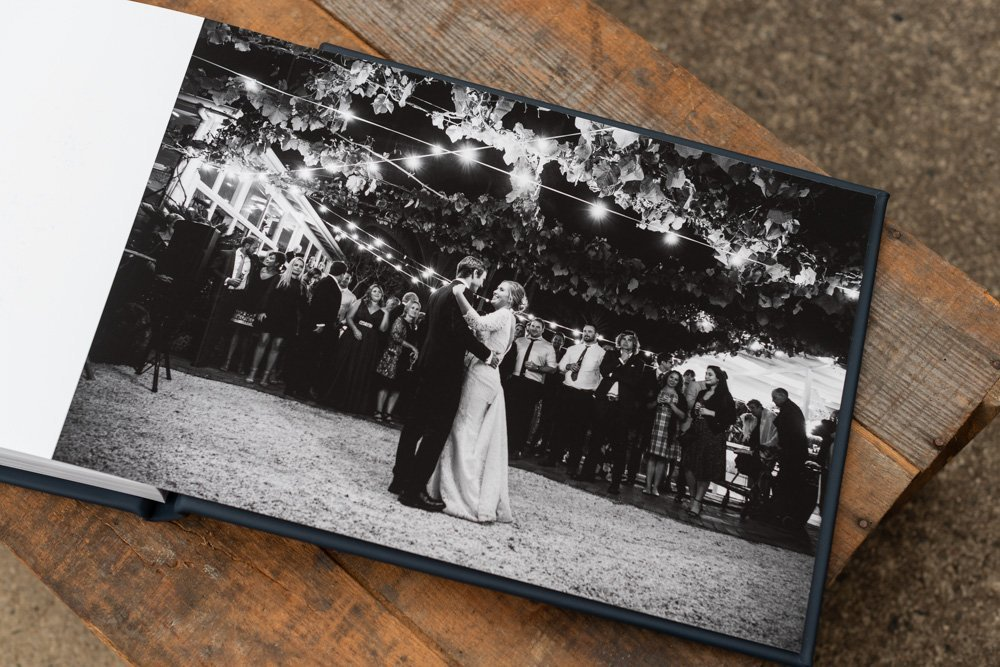 Leather Wedding Photo Album in Navy Blue with Custom Name Embossing - Spread from Bride & Groom's First Dance under Festoon Lights in Black & White